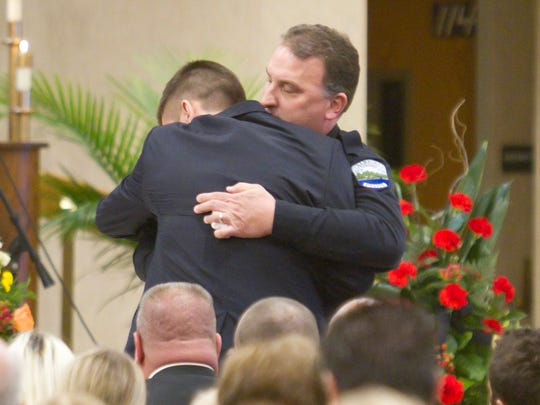 Chief Richard Duffany of the Hamburg Police Department embraces Nick Sanderson after presenting the badge of his father, Sgt. James Sanderson, to him.
