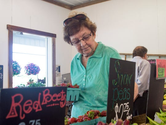 Beryl Myers looks to buys some fresh strawberries and