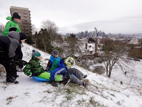 Children sled down one of Seattle's steeper hills and
