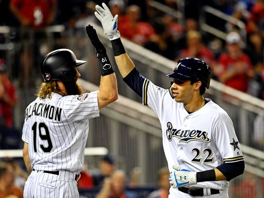The Brewers' Christian Yelich is congratulated by the Rockies' Charlie Blackmon after hitting a home run in the eighth inning,