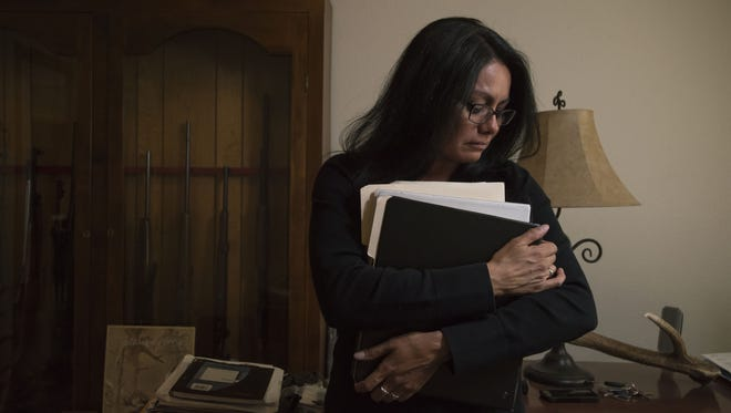 Lydia Lerma, the mother of the first victim who came forward in a child sexual assault case against Andrew Vanderwal, begins to cry on April 10, 2018, while clutching folders containing evidence she had collected during her hunt for Vanderwal, in the home office at her home in Fort Collins, Colorado.