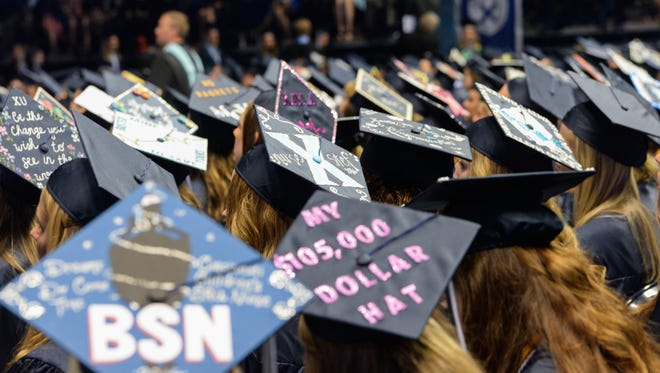 Students wear decorated graduation caps during the Xavier University commencement at the Cintas Center.