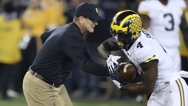 Michigan coach Jim Harbaugh hands off to De'Veon Smith before action against Iowa on Saturday, Nov. 12, 2016 in Iowa City, Iowa.