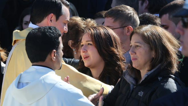 Anamarie DiPietro Hochman, right, and her daughter Samantha are greeted by Rev. Christopher Monturo, left and other clergy as they leave the funeral for her daughter and sisters Alissa and Deanna Hochman at St. Gregory the Great Roman Catholic Church in Harrison, Feb. 27, 2015.