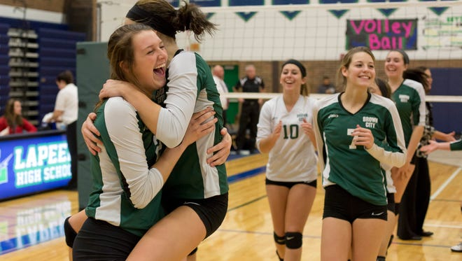 Brown City players celebrate beating New Lothrop in a Class C quarterfinal volleyball game Tuesday, November 17, 2015 at Lapeer High School.