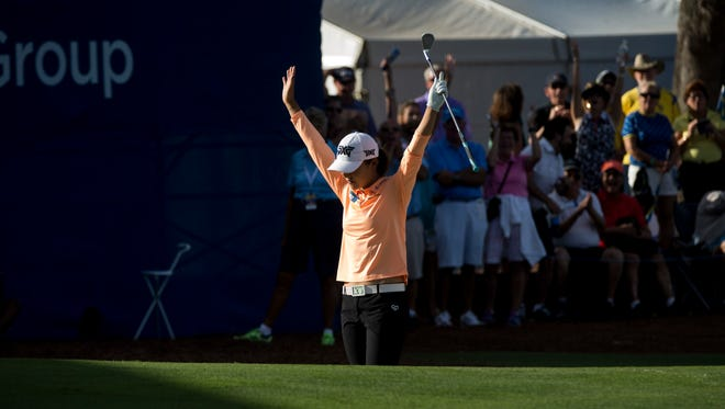 LPGA tour pro Lydia Ko raises her hands in relief after sinking a long shot from the sand trap to make par on the eighteenth hole during the first round of the CME Group Tour Championship at Tiburon Golf Club Thursday, Nov. 16, 2017 in Naples. Ko would finish the day tied for third with a score of five-under par.