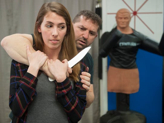 Alyssa DeRosa, 25, of Marlton, demonstrates a self-defense technique used when defending against a knife to the throat from behind, with Don Melnick, owner and instructor of Israeli Krav Maga in Cherry Hill.