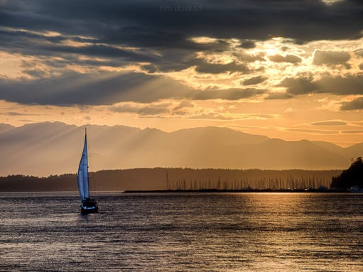 """With rainfall totals well above average for the area, Seattle was happily treated to an entire weekend of much needed sunshine. I snapped a photo of these lucky sailors as they headed back into the Smith Cove Marina on Friday night."""