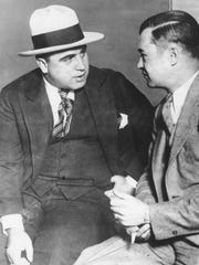 Al Capone, called before a grand jury, talks to an unidentified man in Chicago, Ill., on March 21, 1929. Capone was charged with tax evasion in 1931 and sentenced to 10 years in prison. (AP Photo)
