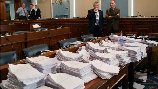 This May 15, 2013, file photo shows stacks of paperwork awaiting members of the House Agriculture Committee as it meets to consider proposals for the 2013 farm bill. Members of the House and Senate are scheduled to begin long-awaited negotiations Wednesday on the five-year, $500 billion farm bill.