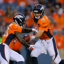 DENVER, CO - AUGUST 23:  Quarterback Peyton Manning #18 of the Denver Broncos hands off to running back Ronnie Hillman #23 during a preseason game at Sports Authority Field at Mile High on August 23, 2014 in Denver, Colorado.