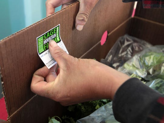 Maria Olvera labels a CSA box with a Sage Mountain Farm sticker on March 6, 2015.