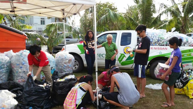 In this March 5, 2017, file photo, Peggy Denney from i*recycle Guam directs student volunteers for recycling at the Paddles Against Cancer event at Matapang Beach.