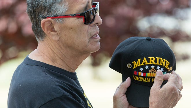 U.S. Marine Corp veteran Richard Sanchez, takes his hat off and points to the insignia while talking with his twin brother U.S. Navy veteran William Sanchez, (not pictured) during the eighth annual Welcome Home Vietnam Veterans event at Veterans Memorial Park on Saturday, March 31, 2018. The twins served in Vietnam together.
