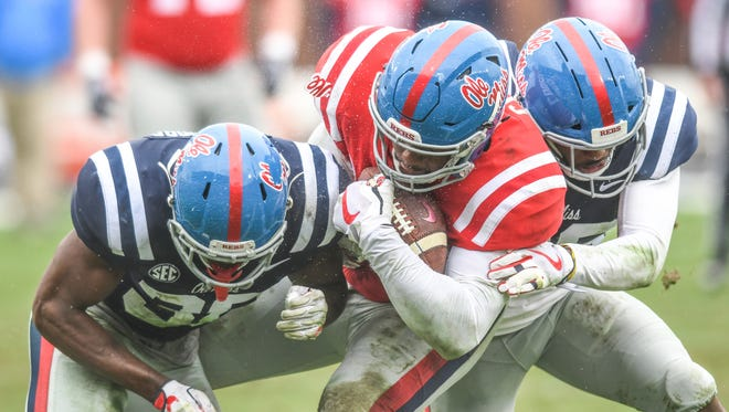 Ole Miss' Octavious Cooley (15), center, is tackled by C.J. Moore (38), left, and Zedrick Woods during Grove Bowl spring NCAA college football game at Vaught-Hemingway Stadium in Oxford, Miss. on Saturday, April 7, 2018.