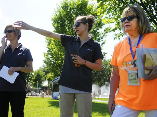 Cindy Hawker, who organizes Middletown Market, talks to Xcel Energy subcontractors Kara Tuttle and Cat McNerlin about their booth setup on July 22 before Summertime by George!