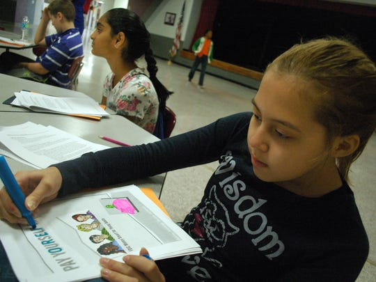 Sixth grader Lily Alvarado colors her financial literacy book at Rucker-Stewart Middle School in Gallatin on Wednesday. Schoolmate Maitri Patel sits to the right.