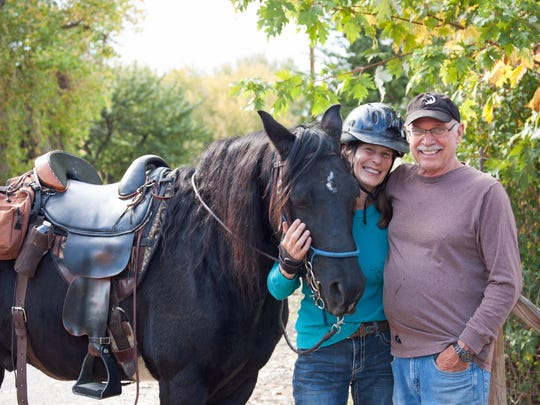 A mutual passion for horses brought together Jody and Bob Carman. The couple stand for a photo on Oct. 17 at their home outside Aztec with one of their horses, Rambler.