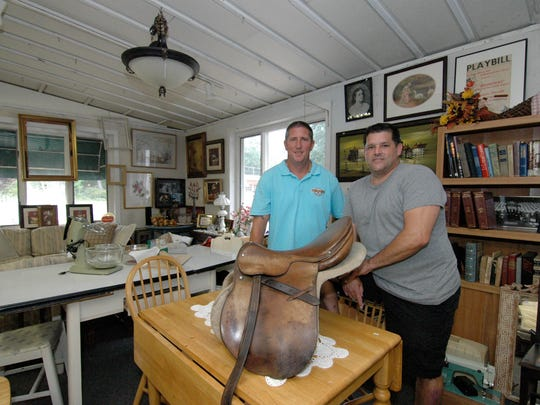Treasures From the Attic Partners Wayne Maver (right) and Dan Flagg inside their storefront location  on Route 206 in Tabernacle. In the foreground is a 1930's vintage leather Swiss Army saddle, along with various other collectibles from estate clean out projects.