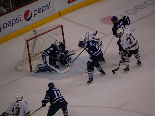 Zack Sill, left, in white, and Aaron Ness (27) set up in front of Toronto's goal on a Hershey power play Saturday night. The Bears defeated the Marlies, 3-2 in overtime.