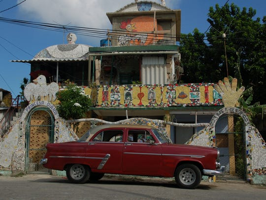 A Ford 1954 four-door sedan is parked in front of the home in the Jose Fuster Neighborhood. The home is decorated with ceramic mosaics.