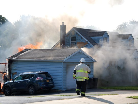 Firefighters battle a fire in a single family home