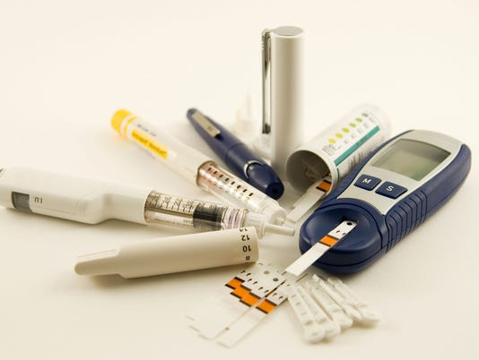 Diabetic medication supplies laid out on white background