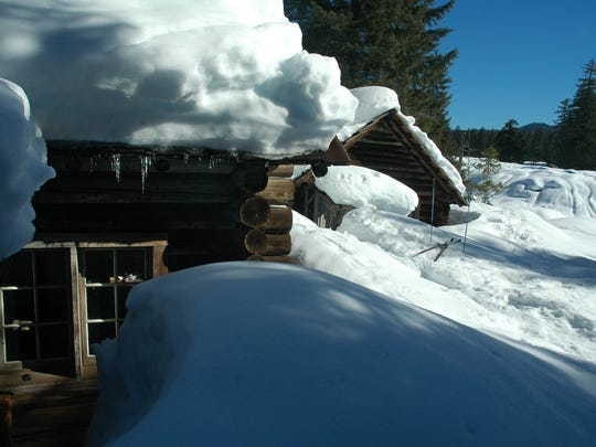 Snow piles up at a rental cabin at Fish Lake. The cabins are a mile hike via snowshoe from Highway 20.