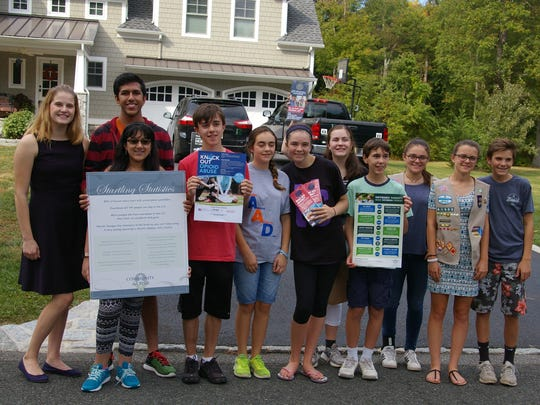 Youth volunteers assist Community in Crisis in Bernards on Knock Out Opioid Abuse Day, hanging door hangers on front doors across dozens of neighborhoods with messages about the dangers of misusing prescription pills.