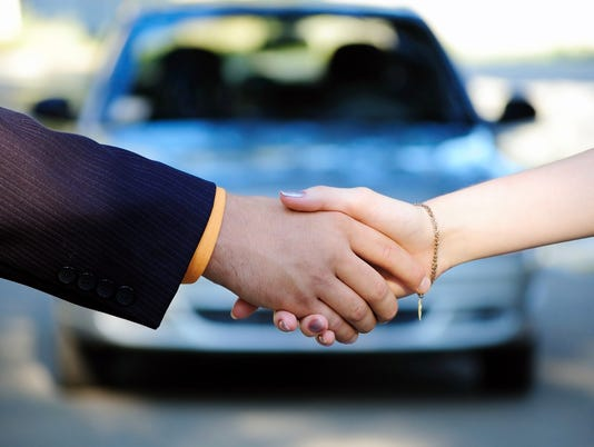 People shaking hands in front of a car after a car sale