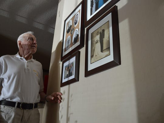 Joseph Vogel, a 94-year-old World War II U.S. Navy veteran, looks at old photographs of his father, who was in the U.S. Army, and of he and his late wife Eileen, hung along his wall in his SouthWood apartment.