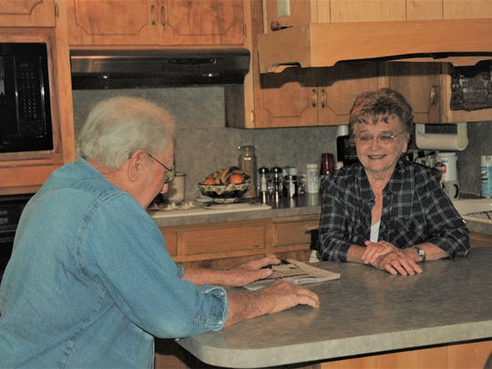 Erwin Weiershausen and wife, Carolyn, plan their day's activities at the kitchen table.