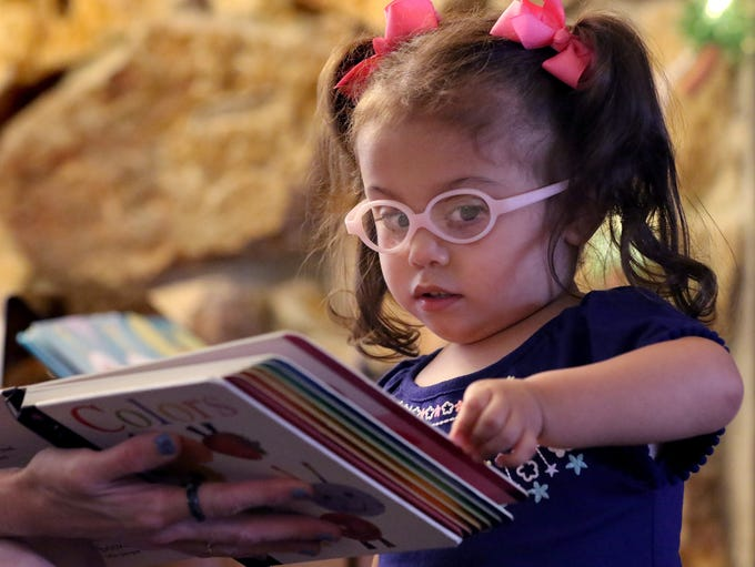 Eleanna Rivas, 3, turns the page of a book that contains