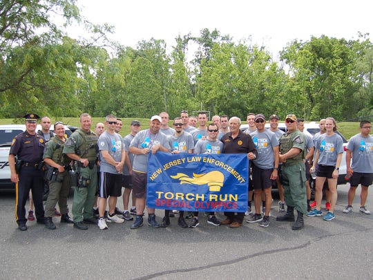 """Twenty (20) members of the Somerset County Sheriff's Office ran in the 2018 Torch Run for Special Olympics New Jersey. Sheriff Frank J. Provenzano, holding the banner on the right, met with his officers before their journey in the ShopRite parking lot in Bound Brook. More than 3,000 New Jersey officers took to the streets of their local communities on one of 26 separate routes to help carry the """"Flame of Hope"""" to the Special Olympics New Jersey Summer Games."""