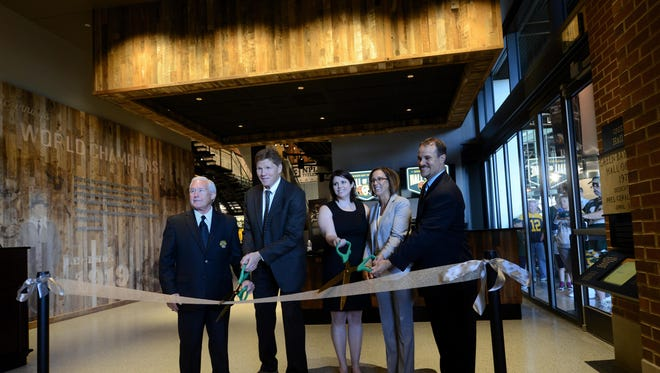 A group including Packers Hall of Fame President R. Perry Kidder (left) and Packers President and CEO Mark Murphy cut the ribbon to open new Packers Hall of Fame inside Lambeau Field in Green Bay.