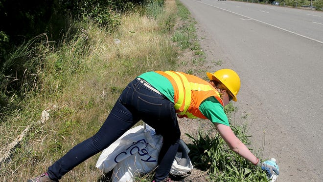 Stella Rillie, 14, from Port Orchard stretches out to pick up litter along the side of southbound Highway 3 south of Naval Base Kitsap-Bangor on Friday afternoon.