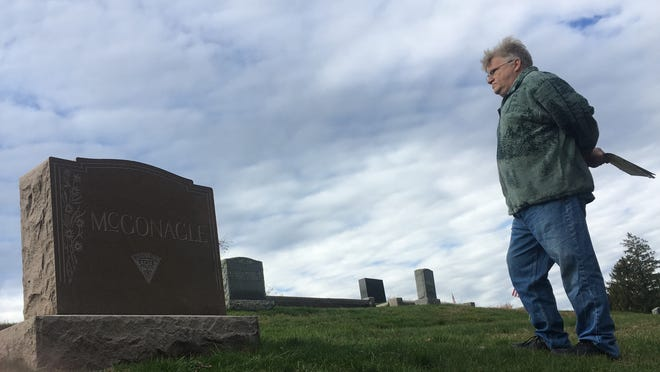 Sean Lovett looks over the famly plot in St. Joseph's Cemetery. The local man said his family was surprised to find someone already buried in his mother's rightful resting place there.