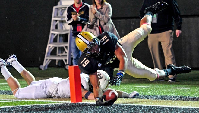 Vanderbilt wide receiver C.J. Duncan, right, dives into the end zone for a touchdown past Charleston Southern's D.J. Curl.