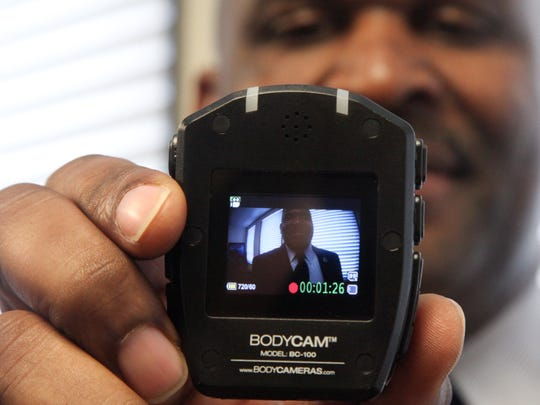 Monroe Police Department Chief Quentin Holmes demonstrates how to use the new body cameras that five officers will wear through May. After an evaluation of the officers' experiences with the selected body camera model, the department plans to distribute a camera to every officer.