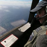 The Royal New Zealand Air Force P-3 Orion's captain, Wing Cmdr. Rob Shearer, watches out of the window of his aircraft while searching for the missing Malaysia Airlines Flight MH370 in the southern Indian Ocean, Monday, March 31, 2014.