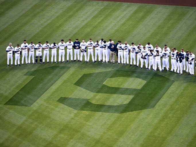 San Diego Padres players and coaches bow their heads during a moment of silence next to a #19 painted on the field as a tribute to Tony Gwynn #19 before a baseball game between the San Diego Padres and the Seattle Mariners.