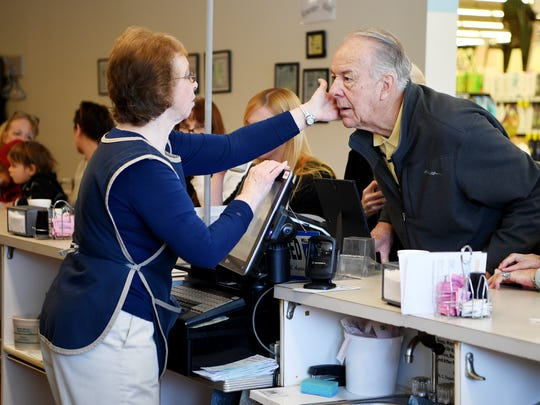 """Gnelle Israel pats Jack Wilkins on the cheek as he and his wife, Janis, pay for their meals at the Rite Aid Coffee Shop March 31, 2018. Israel has worked at the lunch counter for almost 50 years. """"We've become pretty good friends over the years,"""" said Wilkins."""