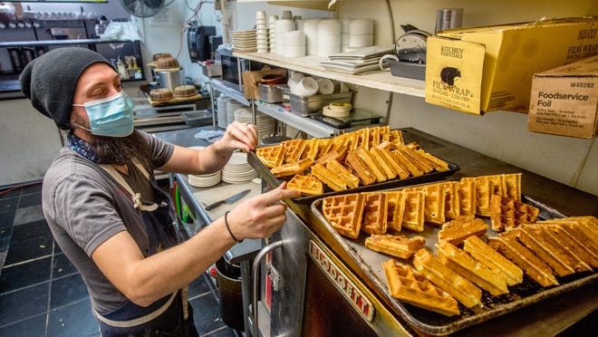 Sous chef Brendan Gregory prepares a batch of waffles for a waffles and chicken dish Thursday, Nov. 12, 2020, at Hearth Restaurant, 4604 N. Prospect Road, in Peoria Heights.