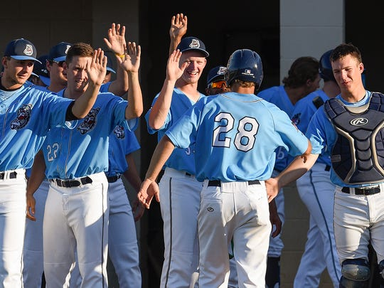The St. Cloud Rox's Luke Ringhofer is met by teammates after scoring against Rochester during the first inning Friday at Joe Faber Field in St. Cloud.