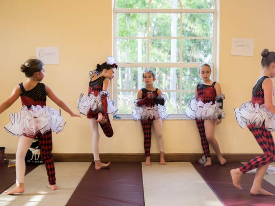 "A group of jesters scratch before they are called to perform their dance number during Etudes de Ballet's ""Cinderella"" dress rehearsal at their dance studio on Wednesday, May 2, 2018."