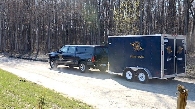 Michigan State Police crime lab vehicles on scene near where a body was found on Friday afternoon April in Ash Township.