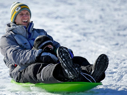 Mark Zurfluh of Appleton, and his son John, go sledding at Plamann Park in Appleton, Wis., Saturday, January 2, 2016.