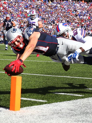 Patriots  receiver Julian Edelman dives into the end zone  past Bills defender Aaron Williams for a 22 yard touchdown.  Williams was injured on the play and left the game on a stretcher. The Patriots be a the Bills 40-32.