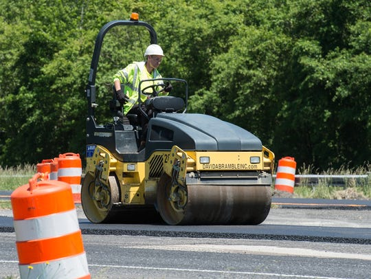A road construction worker uses a steam roller on newly