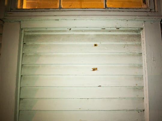 Two bullet holes are seen in the north wall of a home